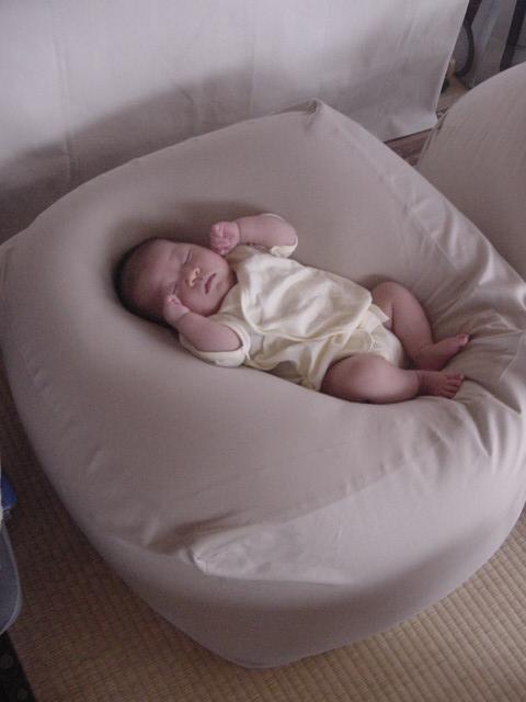 赤ちゃんがベッドのようなベージュのクッションで寝ている