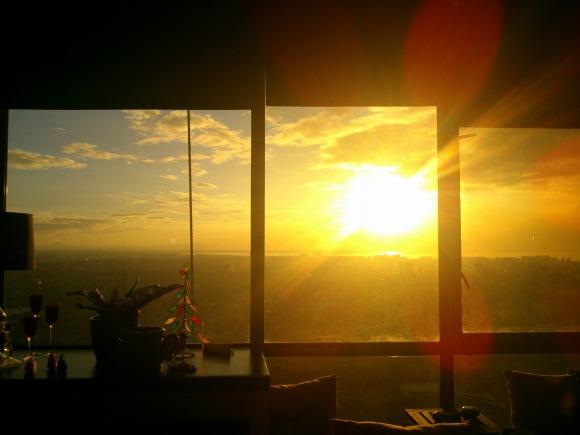 夕焼けでカーテンがない窓